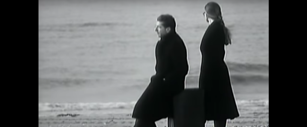 On a beach, a man sits (in profile) on an upright suitcase, and a woman stands behind him on the right. Beyond them is the sea.