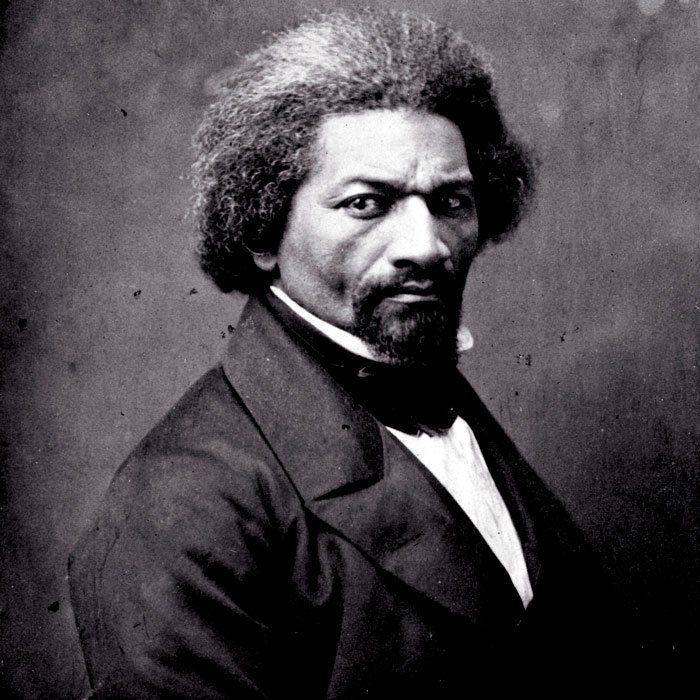 A black man sporting a goatee, his hair beginning to go gray, stares straight into the camera. This is Frederick Douglass.