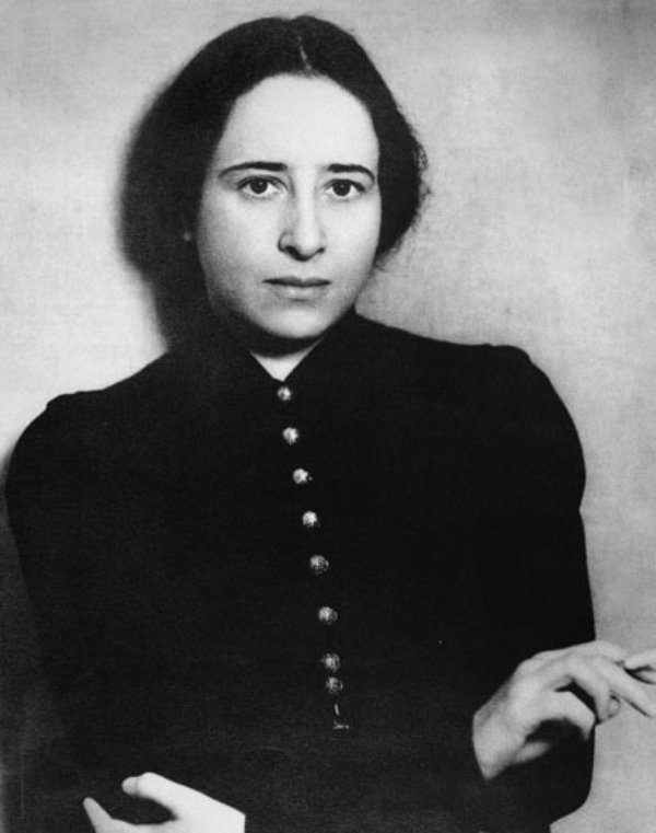 A woman wearing black poses for the camera with arms folded, a cigarette in her right hand.