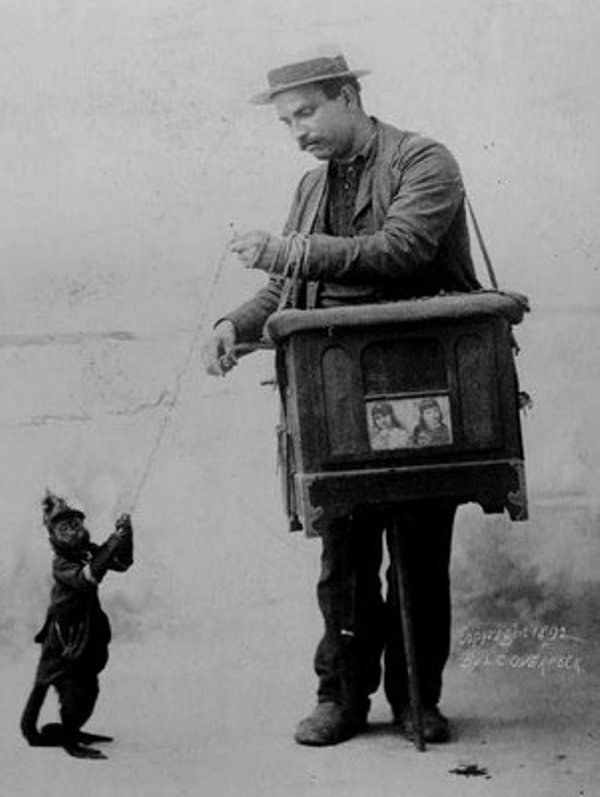 A man stands on the right with a street organ slung over his shoulder. A monkey stands on the left. Each holds one end of a string.