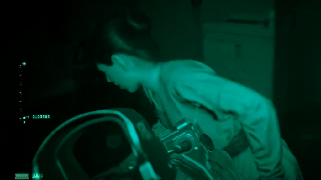 A woman, viewed both through night vision goggles and the sights of a rifle, runs left.