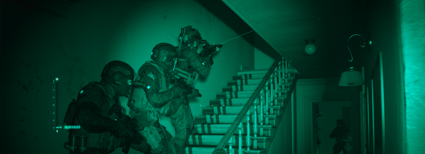 Three men in full military gear stack up at the bottom of a townhouse stairwell, preparing to move to the upper floors.