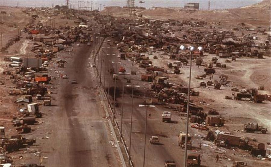 Hundreds (if not thousands) of destroyed vehicles line a desert highway.