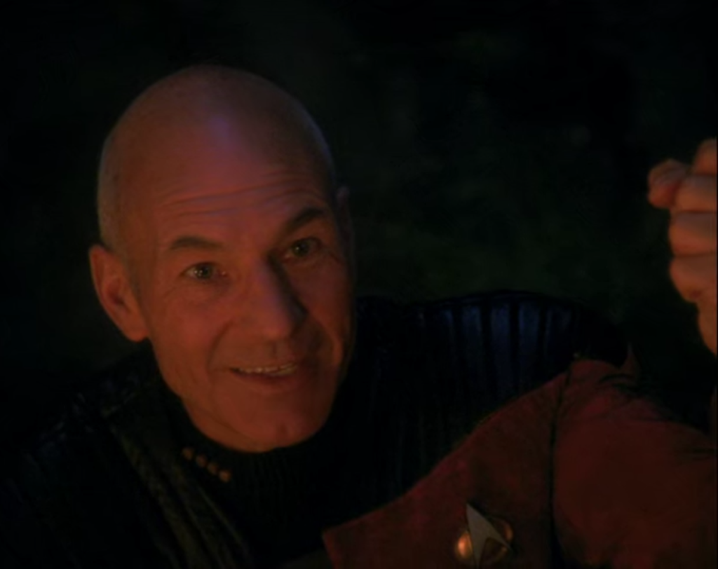 Picard, illuminated by an off-screen campfire, smiles as he looks slightly right of frame, left hand upheld, clenched into a fist.