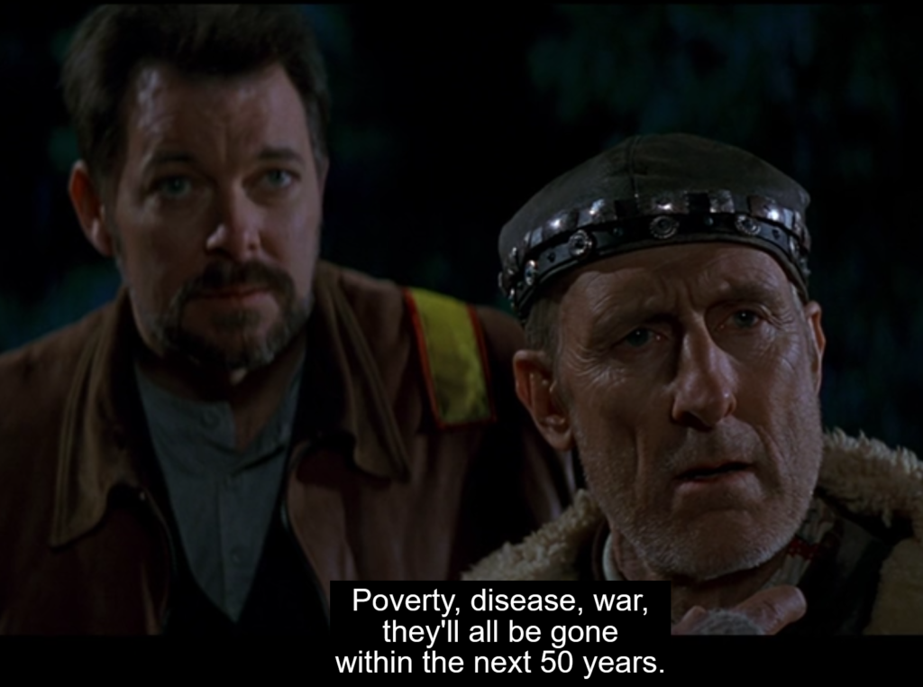 """Riker and Zephram Cochrane look slightly right of frame, listening to someone speaking off-screen. A subtitle at the bottom reads, """"Poverty, disease, war, they'll all be gone within the next 50 years."""""""