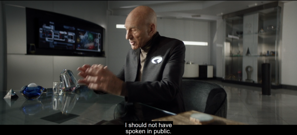 """Picard seated at a desk, making a placating gesture with both hands. A subtitle at the bottom reads, """"I should not have spoken in public."""""""