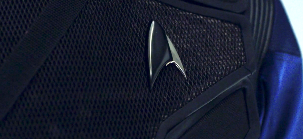 A black version of a Starfleet badge pinned on the chest of a black, futuristic military uniform.