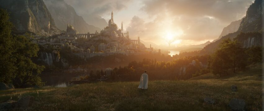 A lone figure stands in a green field looking out across a landscape dominated by a great city on a hill zlightly left of center, and two trees beyond it, one dark and one blazing with the light of a sun. Mountains frame the scene.