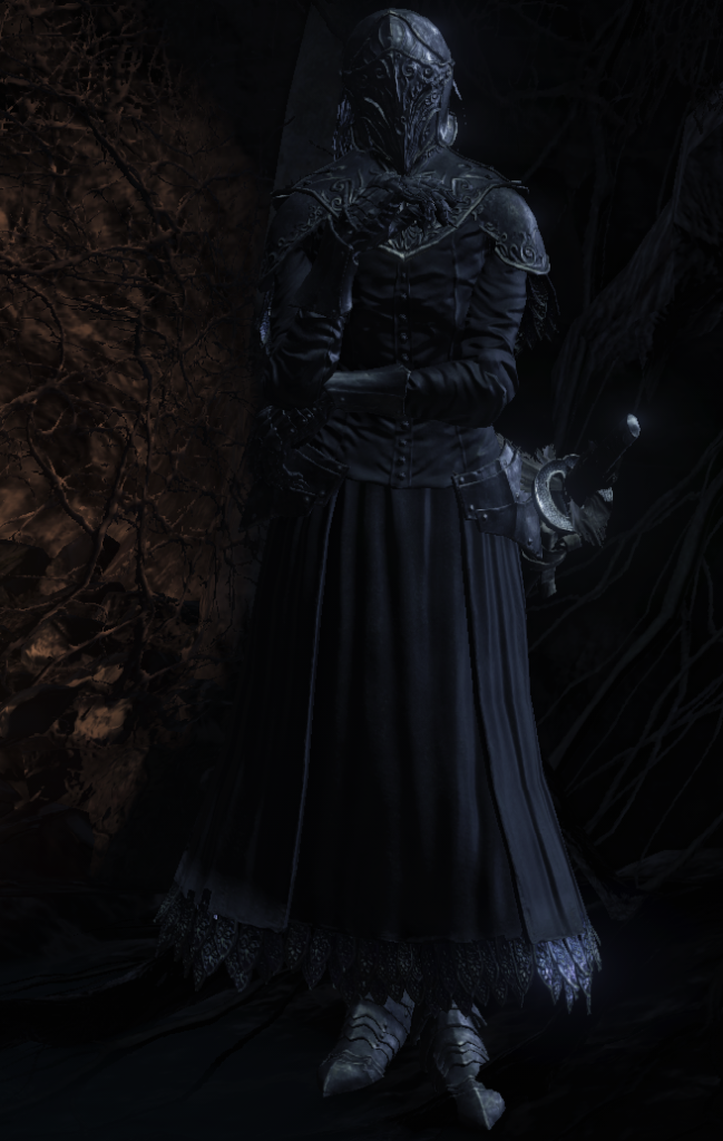 A woman robed all in black, with a helmet and visor completely covering her head, stands in a corner of a cave. A Japanese-style sword hangs from her hip.